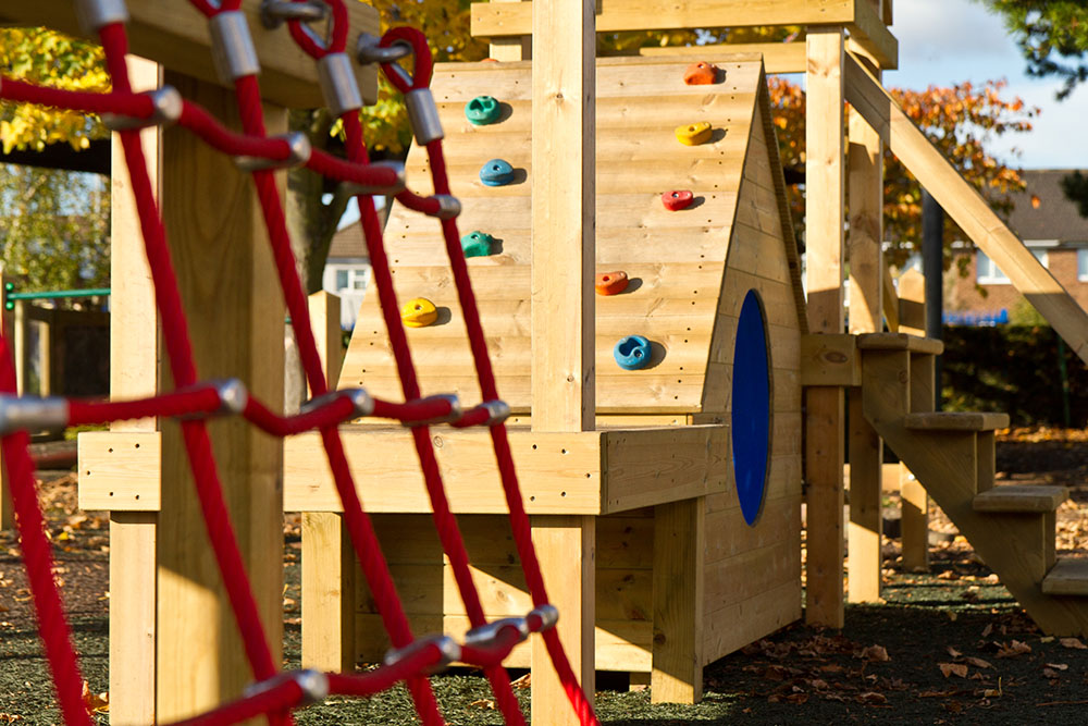 Playground apparatus with wooden climbing wall and climbing netting