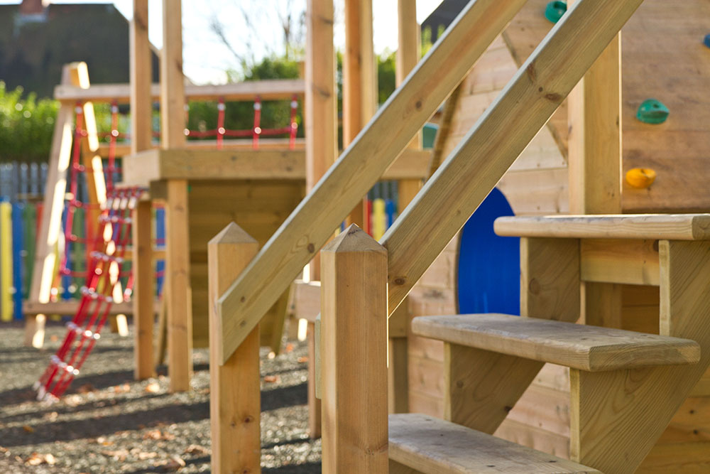 Playground apparatus with wooden steps and swings