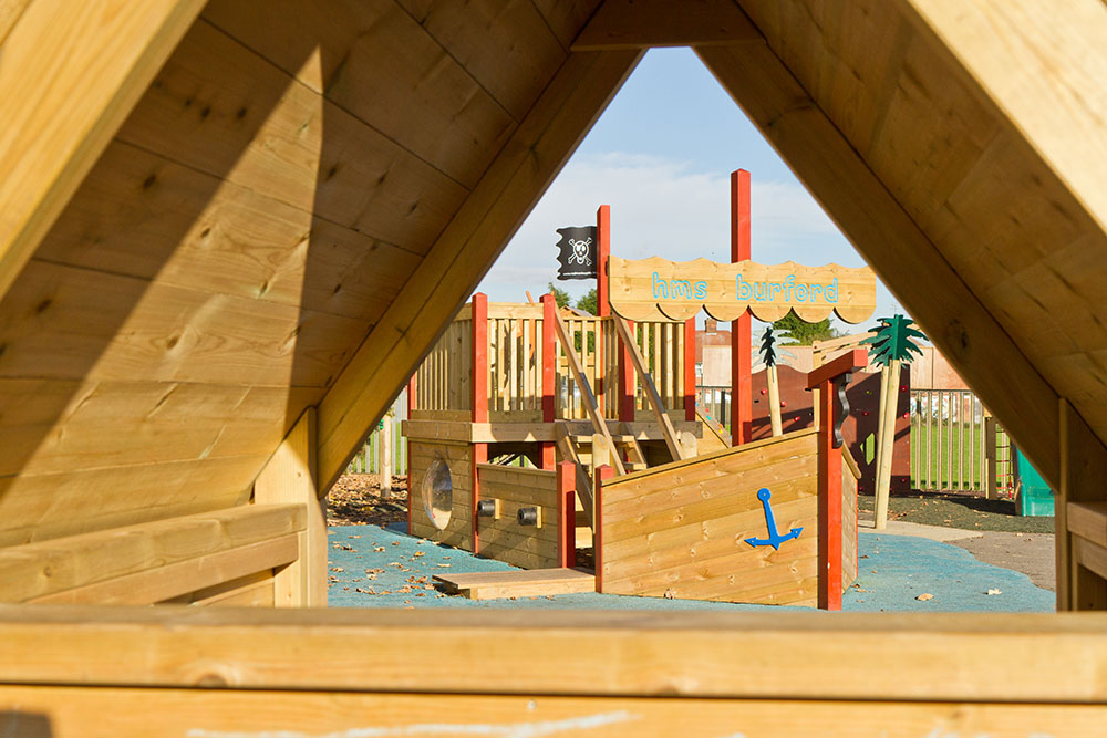 Playground apparatus with wooden pirate ship and shelter